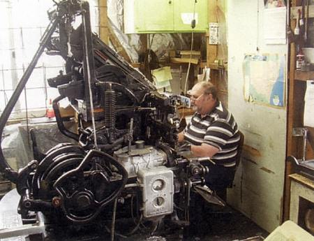 John English seated at a vintage Intertype machine setting next edition's news in lead, tin and antimony at 288 degrees Celsius