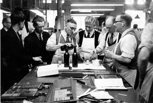 Drinks round the stone to celebrate the banging-out of an apprentice at Argus Press, London, UK, 1950s